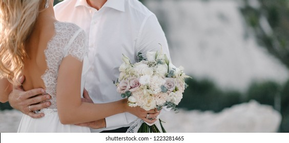 Wedding couple with concealed identity holding hand in evening light