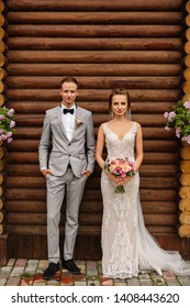 Wedding couple. Elegant bride and groom looking to camera. Portrait of beautiful newlywed couple on wooden background. Rustic wedding concept