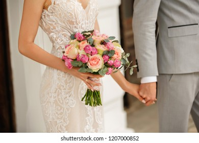 Wedding couple. Elegant groom and bride with wedding bouquet holding hands. Stylish newlywed couple. Marriage concept