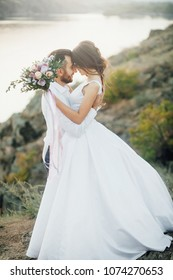 Wedding couple embrance at the walk with mountain and river at the background. Outdoors