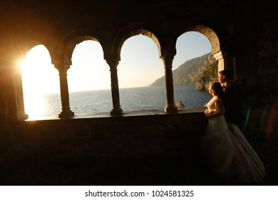 Wedding Couple enjoying sunset in old window at sea