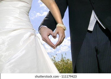 Wedding couple forming heart shape with there palms