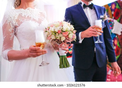 wedding couple with glasses and bouquet