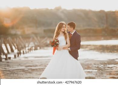 Wedding couple, groom, bride with bouquet posing near sea on sunset