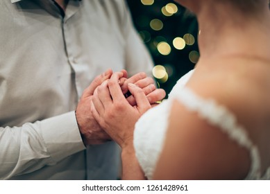 wedding couple hands with lights in background