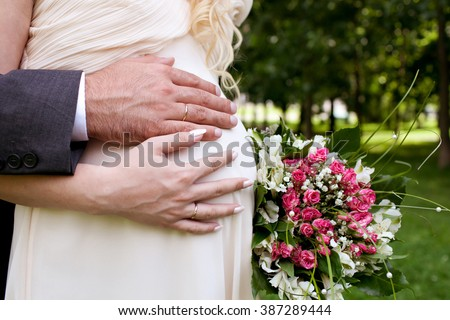 aaac7213e4 Wedding couple hands with wedding rings on woman's pregnant belly