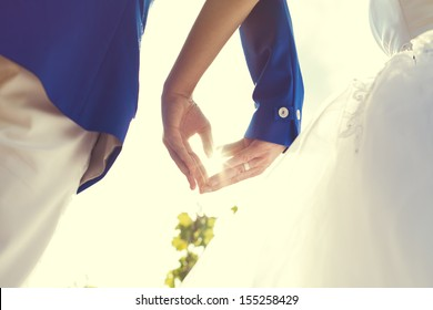 wedding couple hands touching fingers in the shape of hearts. Bright light of the sun on background.