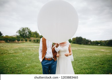 Wedding couple hides behind big white balloon in summer park. Wedding celebration