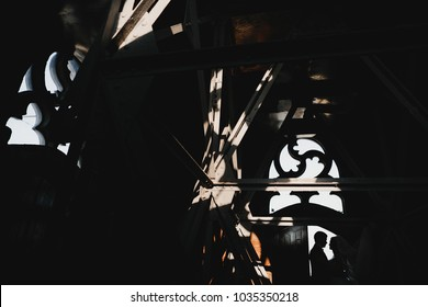 Wedding couple hides in the shadows posing before old wooden doors and window