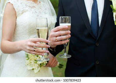 Wedding couple hold glasses with champagne in arms