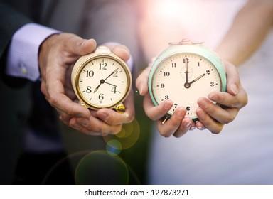 Wedding couple is holding clocks