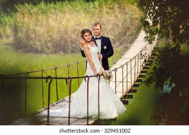 Wedding couple holding each other on suspension bridge