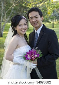 Wedding couple holding flower bouquet smiling in the park