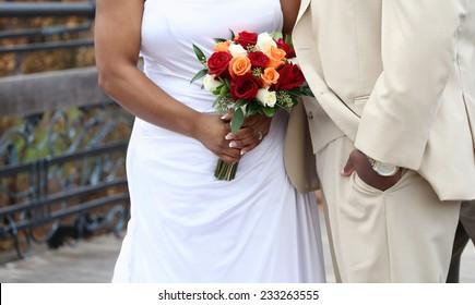 wedding couple holding flowers outdoors