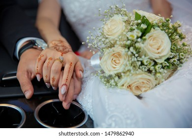 Wedding couple holding hands .Bride and groom hands with wedding rings and bridal dress . Bride and groom's hands with wedding rings