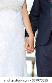 Wedding couple holding hands. Bride and groom holding hands in wedding ceremony.
