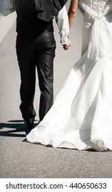 Wedding couple holding hands. Getting married dressed in black and white
