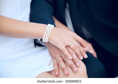 Wedding couple holding hands. Wedding theme. Holding hands newlyweds. Bride and Groom wedding day. Wedding gold rings.