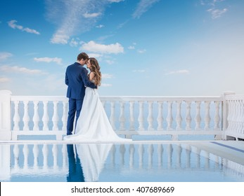 Wedding couple hugging and standing with her back outdoors near the pool. Happy bride and groom in love on their honeymoon. Woman in an elegant dress a man in the suit.