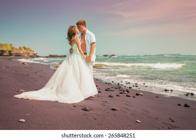 wedding couple just married at the volcanic sandy beach