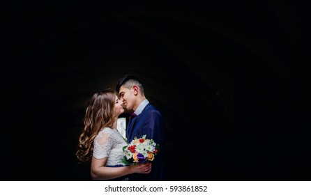 Wedding couple kisses under the archs on black background