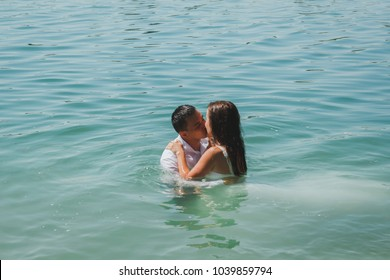 Wedding couple is kissing in azure blue lake splashes of water. Beautiful bride in puffy dress and groom are having fun. Summer passion crazy emotions photo on the seaside. Wet wedding clothes.