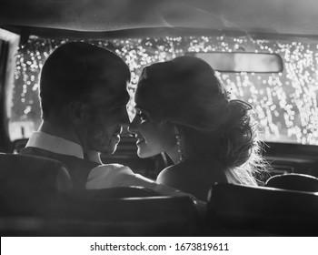 wedding couple kissing in retro car. black and white portrait