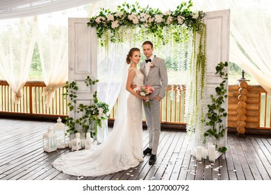 Wedding couple looking to camera near wedding arch after wedding ceremony. Portrait of happy newlyweds couple