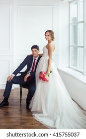 Wedding couple in love. Beautiful bride in white dress with brides bouquet and handsome groom in blue suite embrace indoors in decorated studio room, white bright interior with big window.