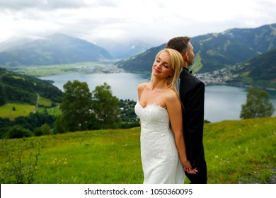 Wedding couple in love kissing and hugging near lake on beautiful landscape