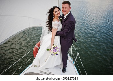 Wedding couple in love at small sailboat yacht on lake.