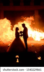 Wedding couple in medieval costumes with vampire style make-up standing in the dark against the backdrop of a big fire, Halloween theme