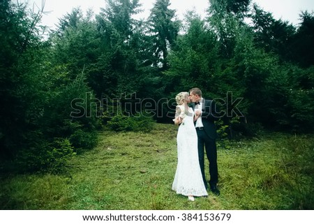 Wedding couple at mountain next to forest lake. Groom and bride