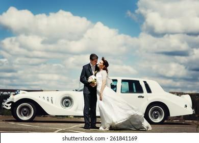 wedding couple near white car, cloudy sky background