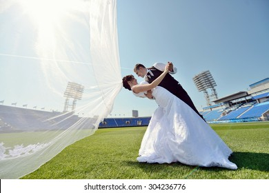 Wedding couple on the football stadium is hugging each other. Beautiful girl in white dress. Man in suit. Beauty bride with groom. Female and male portrait. Woman with lace veil. Lady and guy outdoors