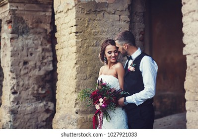 Wedding couple outdoors is hugging each other. Beautiful model girl in white dress. Man in suit. Beauty bride with groom.