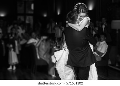 wedding couple performing first dance and hugging. luxury bride and groom embracing. tender sensual romantic moment at wedding reception in restaurant. black white photo