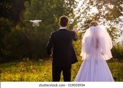 Wedding couple pose for dron photo in autumn nature.