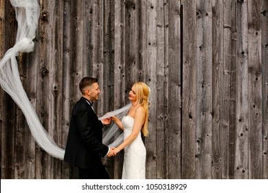 Wedding couple posing in front of Barn Wood Wall