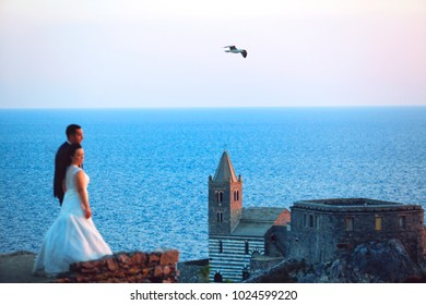 wedding couple posing in front of church on sea background