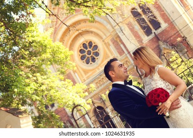wedding couple posing in front of church