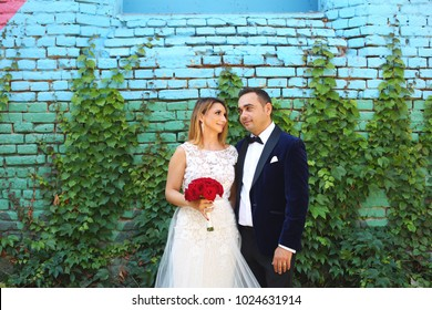 wedding couple posing in front of old colored wall