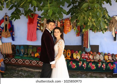 wedding couple posing in front of old traditional shoes, scarfs and bags