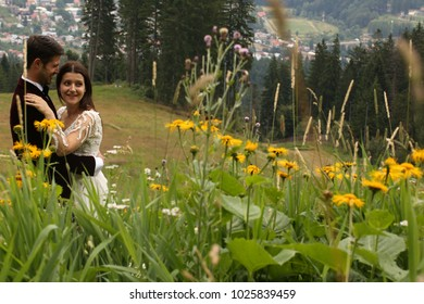 wedding couple posing on green hill with flowers