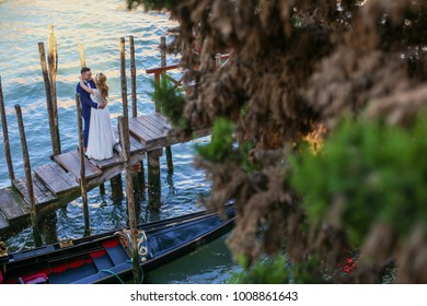 wedding couple posing on old dock near gondola