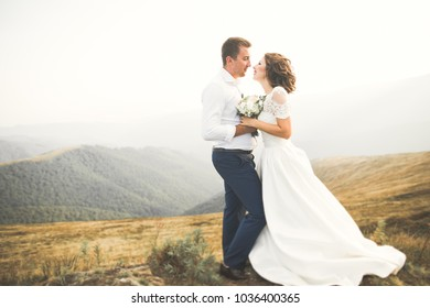 Wedding couple posing on sunset at wedding day. Bride and groom in love