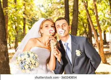 Wedding couple posing with stick lips, mask