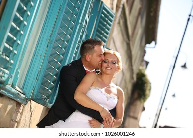 wedding couple posing in sun in front of old window