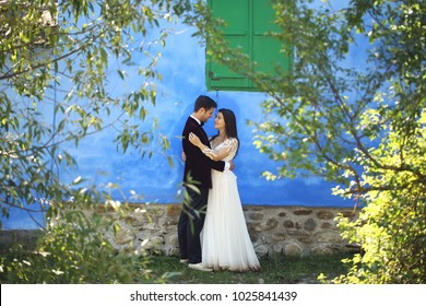 wedding couple psing in front of green windows on the blue wall through the leaf