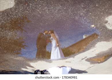wedding couple reflects in a puddle